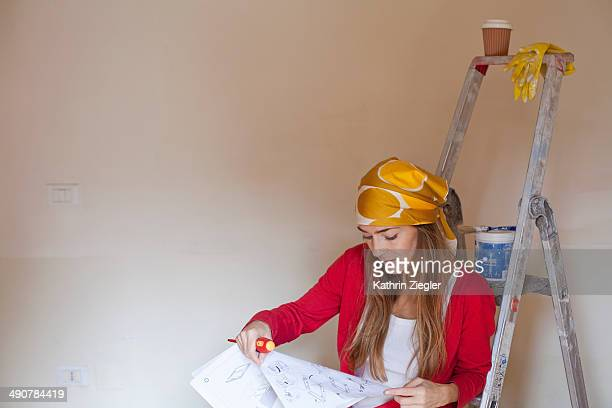 woman sitting on ladder, reading manual