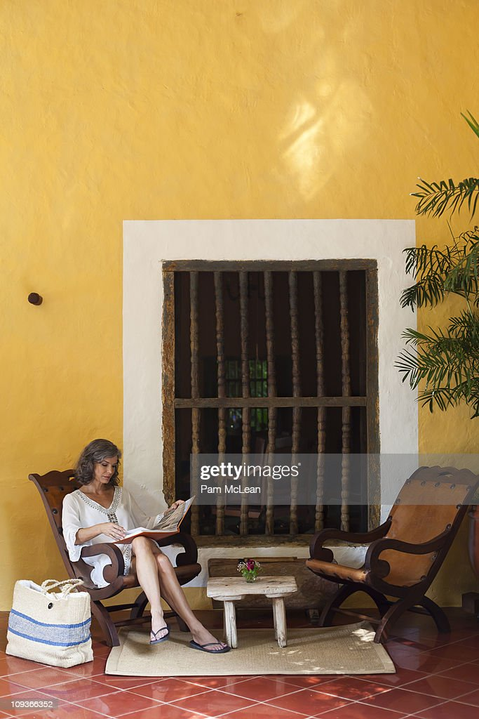 Woman sitting on lanai at resort in Mexico. : Stock Photo