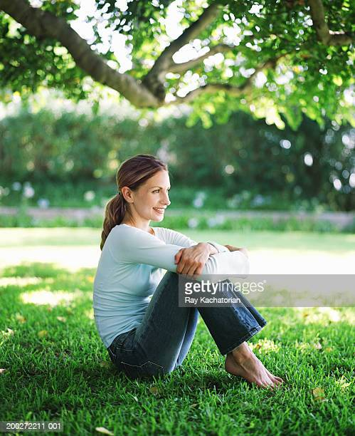 Woman sitting on lawn, arms around legs, smiling, side view