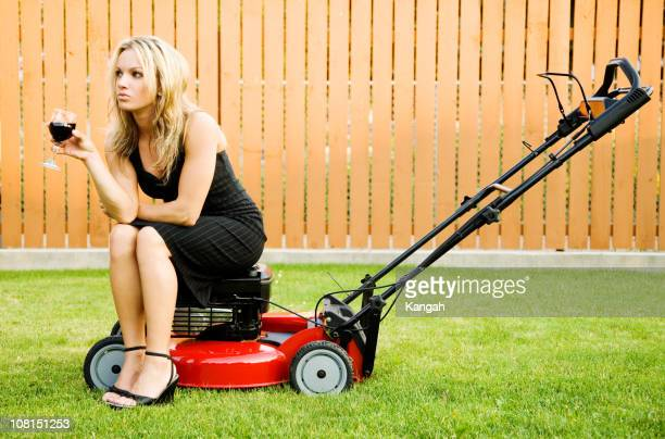 Woman Sitting on Lawnmower Drinking Wine
