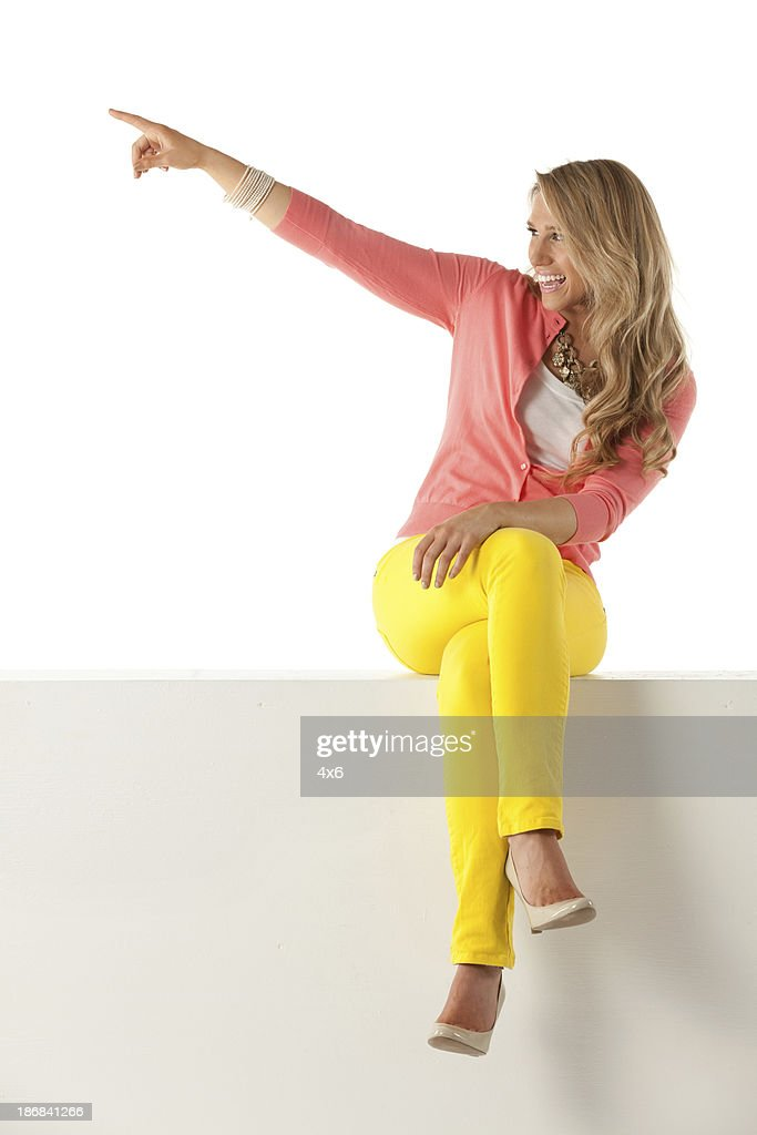 Woman sitting on ledge pointing away