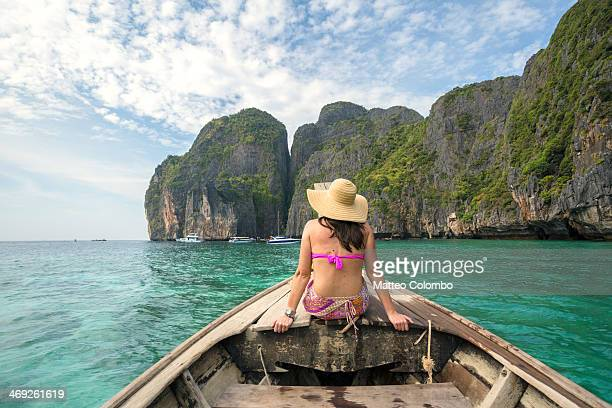 Woman sitting on long tail boat's prow, Thailand