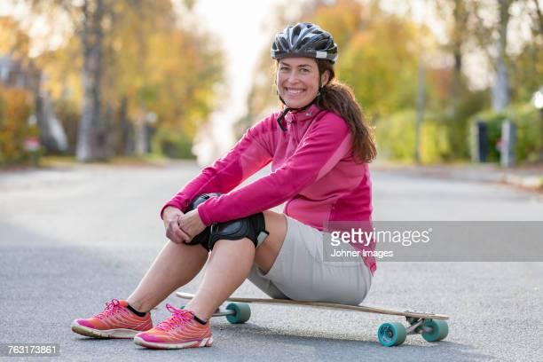 Woman sitting on longboard