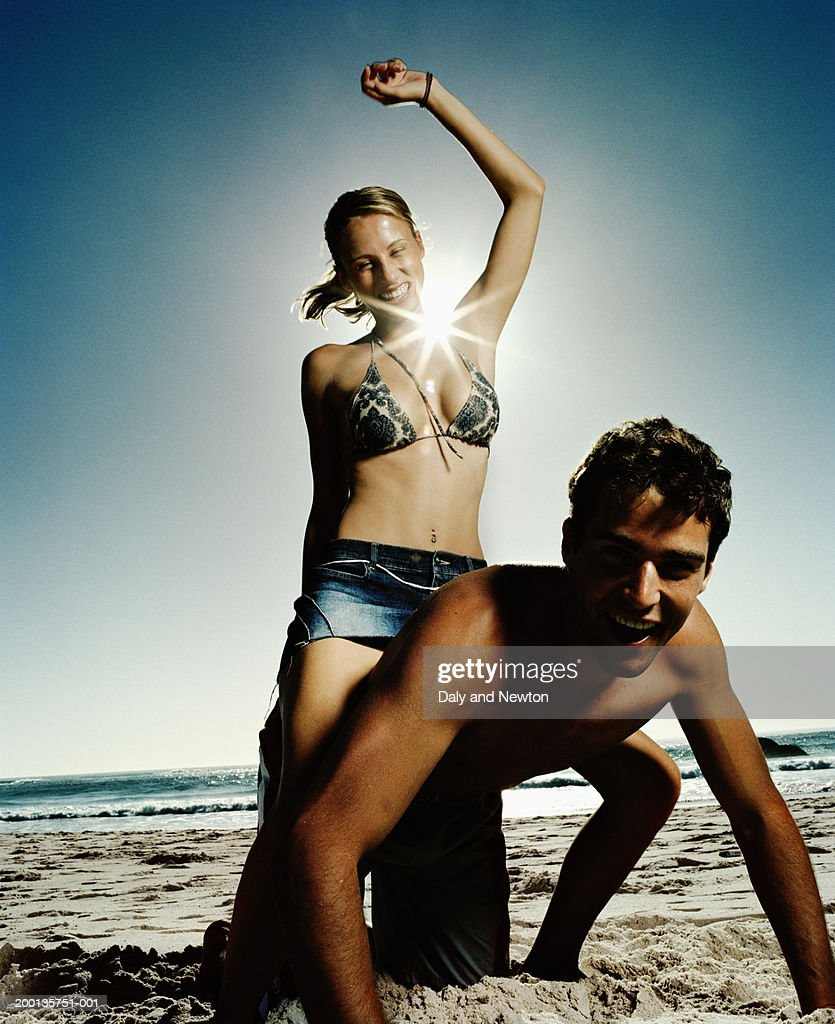 Woman sitting on man's back on beach, laughing : Stock Photo
