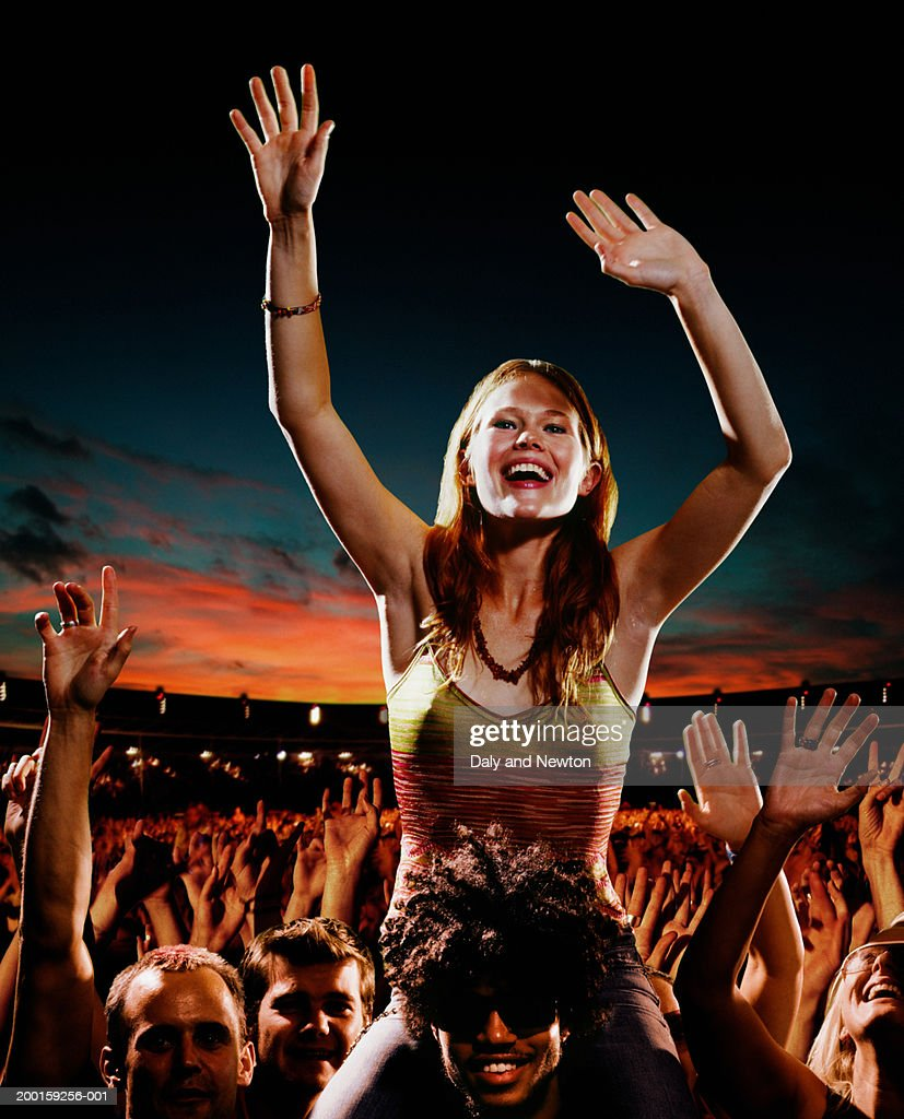 Woman sitting on man's shoulders amongst crowd at concert, sunset : Stock Photo
