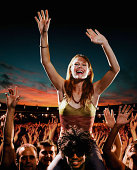 Woman sitting on man's shoulders amongst crowd at concert, sunset