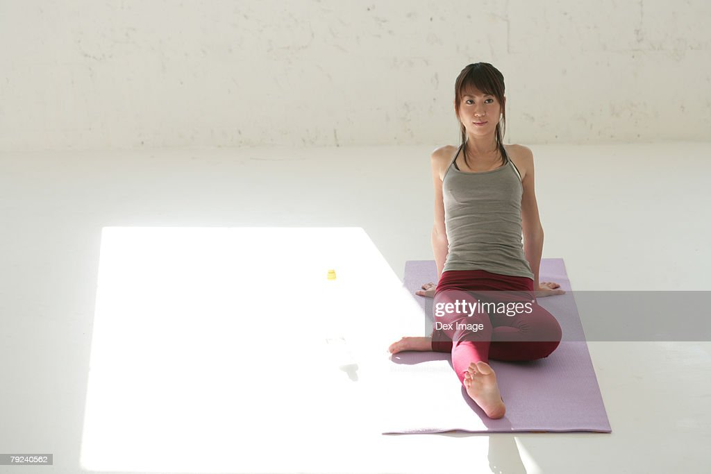 Woman sitting on mat, one leg under the other : Stock Photo