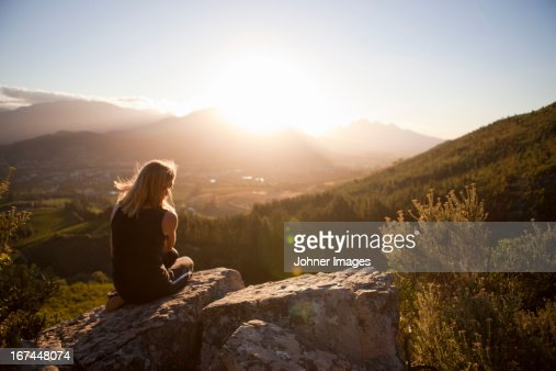 Woman sitting on mountain and looking at sunset : Stock Photo