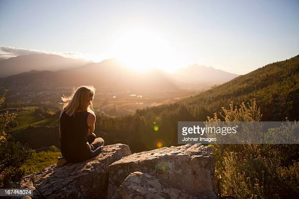 Woman sitting on mountain and looking at sunset