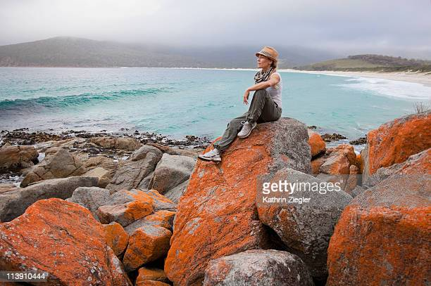 woman sitting on orange algae rocks, Tasmania