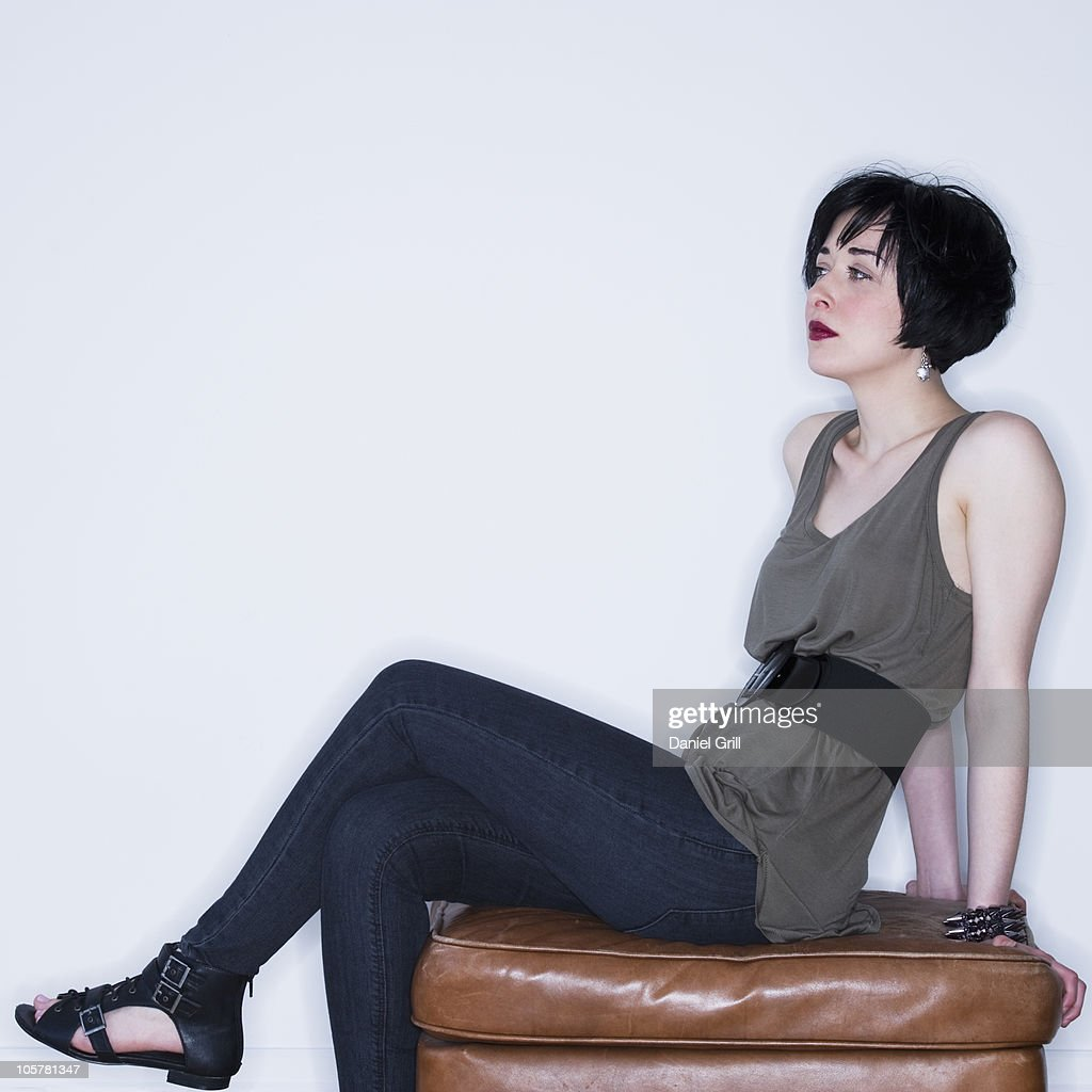 Woman sitting on ottoman stock photo getty images for Ottoman to sit on
