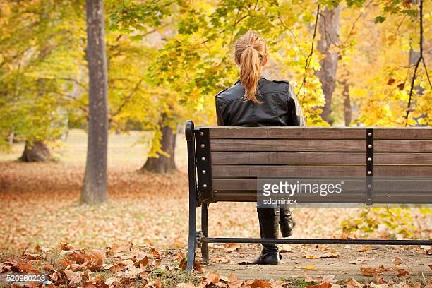 Femme assise sur le banc en profitant de la vue sur le parc en automne