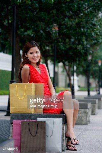 Woman Sitting On Park Bench Shopping Bags Next To Her Stock Photo ...
