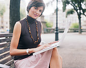 Woman sitting on park bench with laptop, smiling, portrait