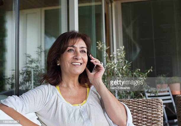Woman sitting on patio talking on cell phone