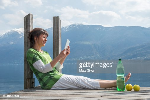 Woman sitting on pier with her computer