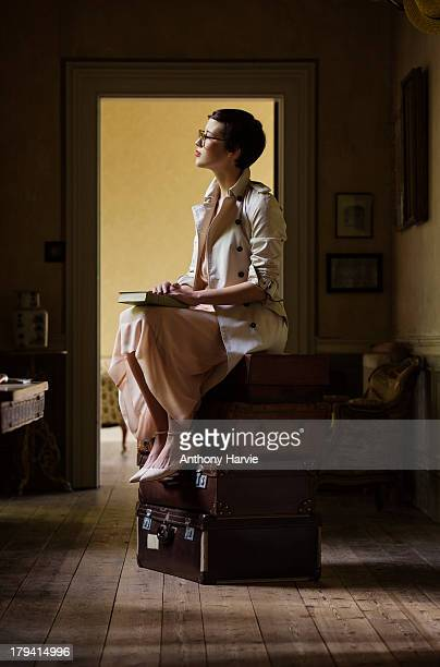 Woman sitting on pile of suitcases