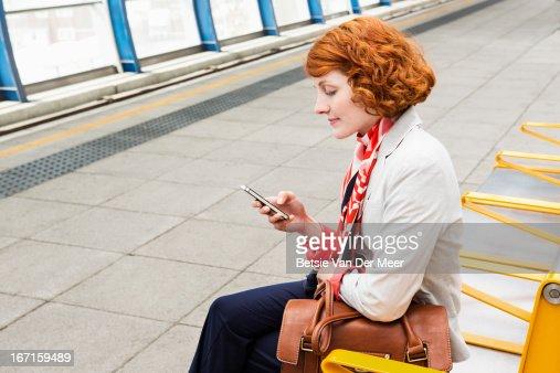 Woman sitting on platform checking phone. : Stock Photo