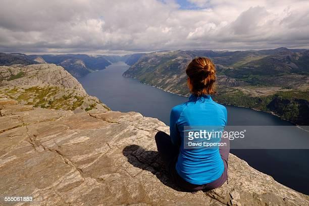 Woman sitting on Pulpit Rock (Preikestolen)