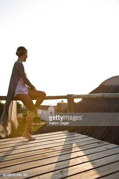 Woman sitting on railings of beach house, side view