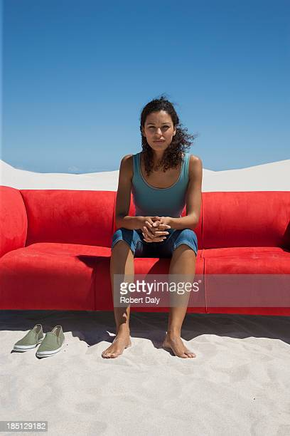 A woman sitting on red sofa in the middle of the desert
