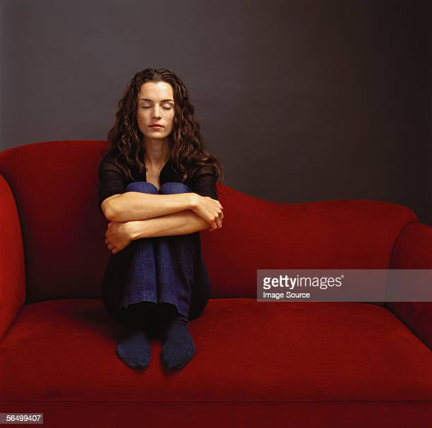 Woman sitting on red sofa