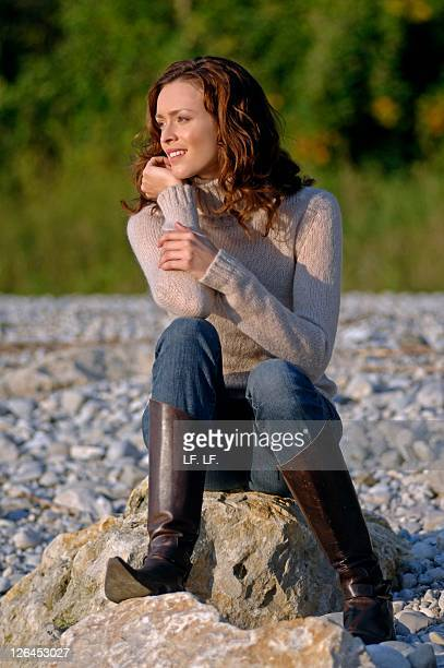 Woman sitting on rock and smiling