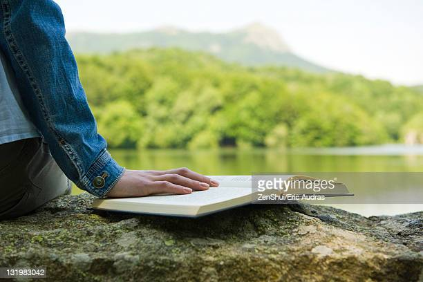 Woman sitting on rock by lake with book, cropped