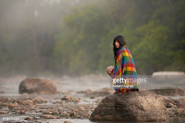 woman sitting on rock in nature