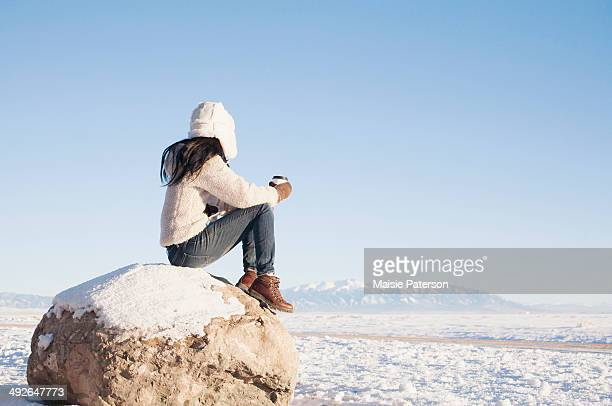 Woman sitting on rock with cup in winter, Colorado, USA