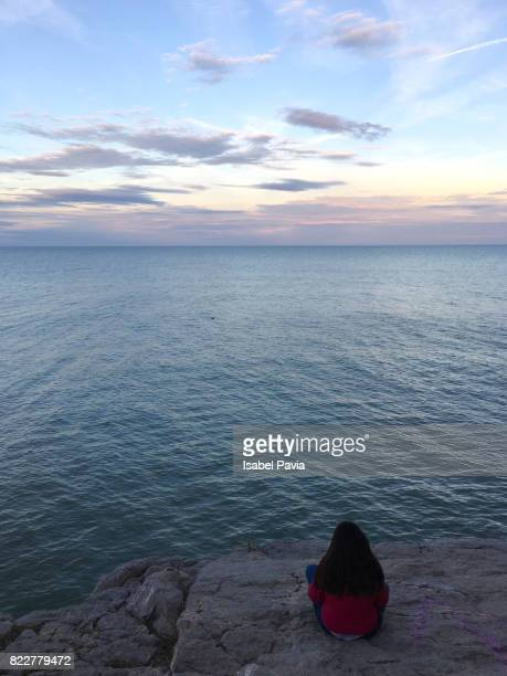 Woman sitting on rocks and looking out to sea.
