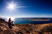 Woman Sitting On Rocks At Lanzarote During Sunny Day