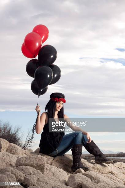 Woman Sitting on Rocks in Nature Holding Balloons