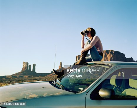 Woman Sitting On Roof Of Car Using Binoculars Side View