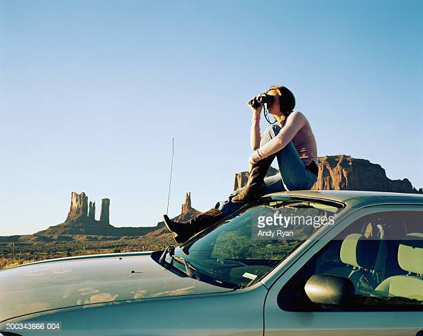 Woman sitting on roof of car, using binoculars, side view