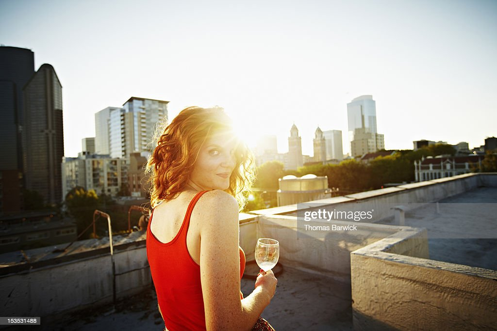 Woman sitting on rooftop at sunset smiling : Stock Photo