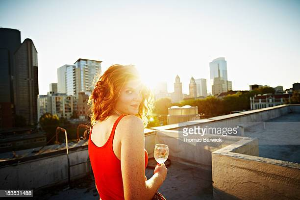 Woman sitting on rooftop at sunset smiling