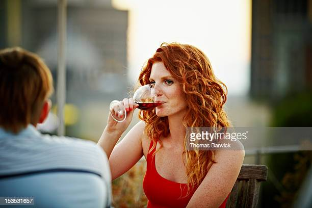 Woman sitting on rooftop deck drinking wine