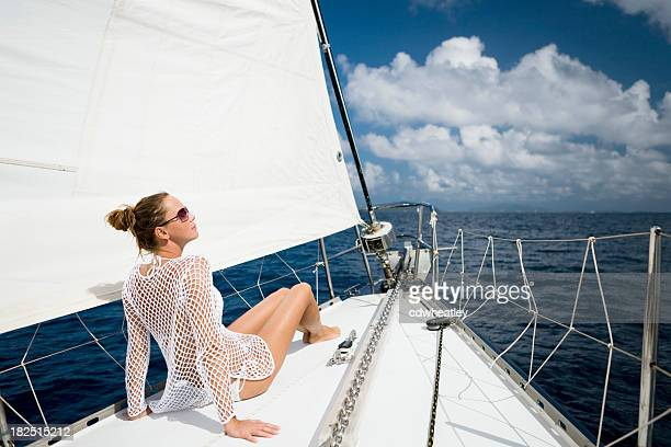 woman sitting on sailboat sailing through the Caribbean