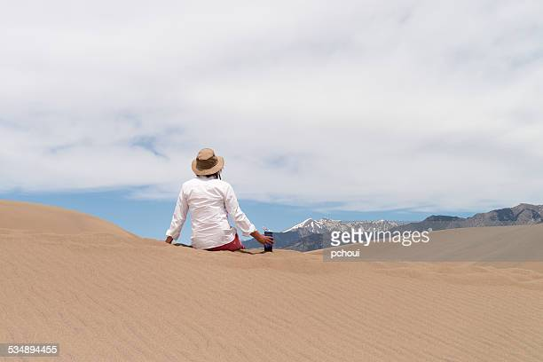 Woman sitting on sand dunes to look at Colorado landscape