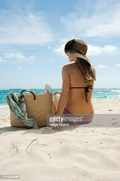 Donna seduta sulla spiaggia di sabbia, Mustique, isole Grenadine