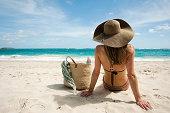 Woman sitting on sandy beach, Mustique, Grenadine Islands