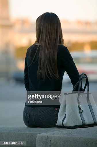 Woman sitting on small wall, rear view