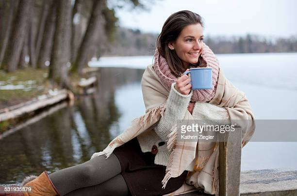 woman sitting on small wooden pier with cup of tea