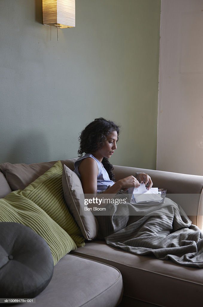 Woman sitting on sofa checking letters : Stock Photo