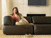 Woman sitting on sofa in living room, portrait