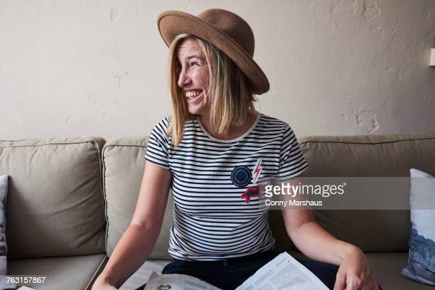 Woman sitting on sofa, newspaper on lap, looking away, laughing