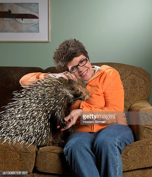 Woman sitting on sofa petting porcupine, smiling
