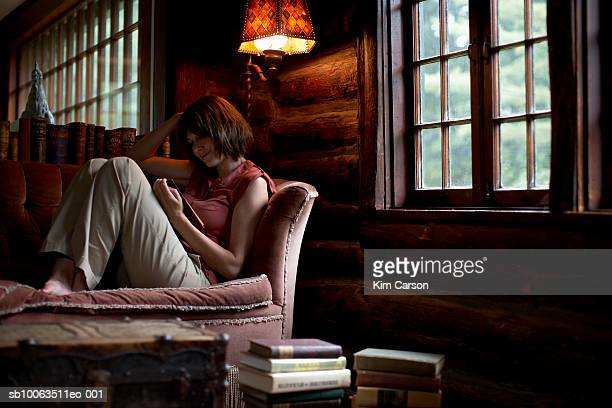 Woman sitting on sofa, reading book