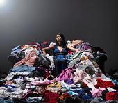 Femme assise sur le canapé, entouré de vêtements.